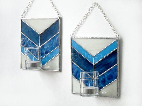 Una coppia di candelieri di parete blu geometrico o monofiore. Sono fatti come circa 6 x 7 pollici pannelli di vetro colorato che tiene un vetro votive. La votiva è rimovibile e può essere utilizzata per tenere una candela o fiori - versare un po acqua e il supporto di candela diventa un vaso gemma. Ogni pannello era costituito da quattro tipi di vetrate: quattro azzurri e un beige chiaro. Ho fatto questo pannello usando la stagnola di rame o metodo di stile Tiffany - così è venuto senza…