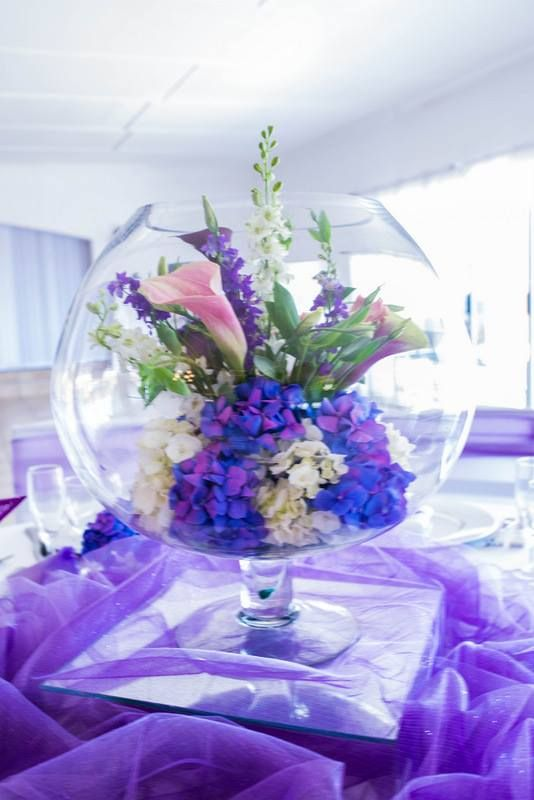 Monte Vista Venue purple centerpiece with a mix of flowers inside a fishbowl, all on a mirror box and purple net.
