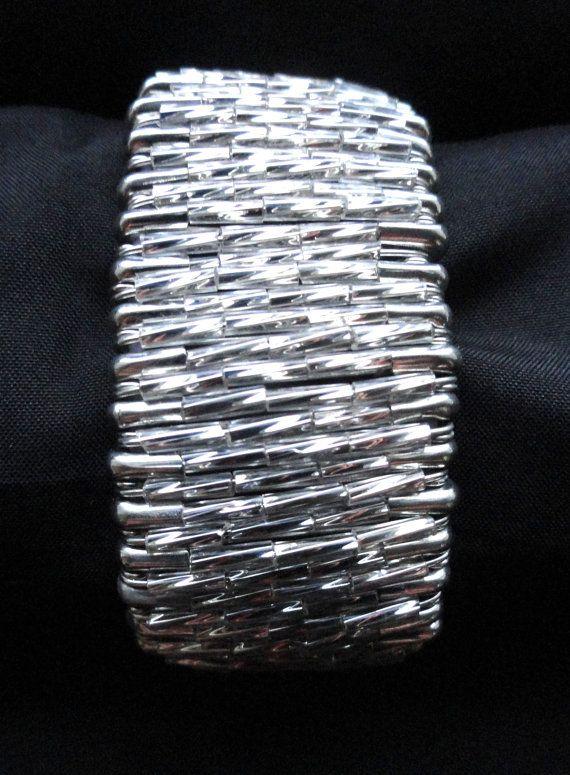 Un bracelet artisanal composé de perles de bugle argenté enfilés sur des épingles de sûreté couleurs argent. Ce bracelet est fait avec environ 80-90 de goupilles de sécurité couleurs argent et perles de bugle argenté. Les perles de bugle tordus sont de haute qualité et donnent le bracelet une superbe texture et la brillance. Les épingles de sûreté sont 27mm de long et enfilée sur une corde élastique stretch. Ce bracelet sadapte facilement sur la main et sadapte à la plupart des tailles ...