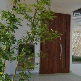 『西条の家』中庭のある家の部屋 木の玄関ドア