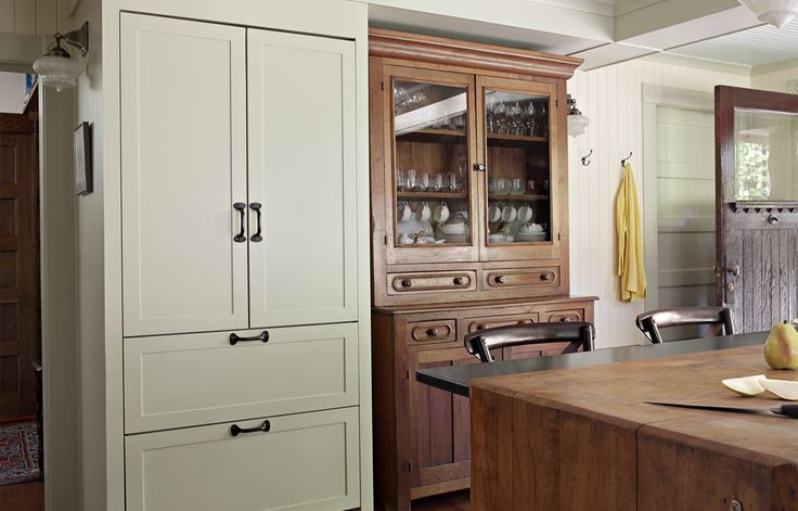 Painted French door panels enclosing the fridge give it a furniture feel so it blends in with the kitchen cabinets. Refrigerator: Liebherr