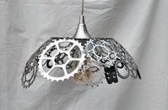 A truly unique lamp for that special bike lover. The shades are made from a variety of bicycle parts. It is comprised of gears, lock rings, bearing races, to even cleat mounts. Half the fun is trying