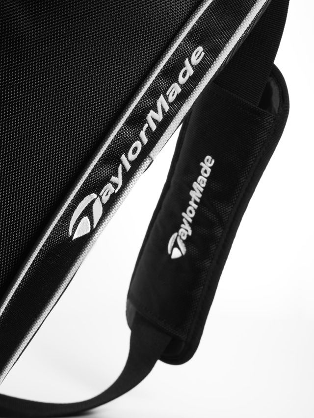 Golf sports bag. Black. Nylon. White piping. Large, zipped main compartment. Additional zipped pockets on front and sides. Detachable shoulder strap. White embroidered Mercedes-Benz logo. White embroidered TaylorMade logo. Made by TaylorMade. Size approx. 56 x 31 x 29 cm.