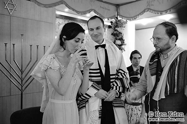 The bride drinks wine under the Chuppah watched by the groom and rabbi