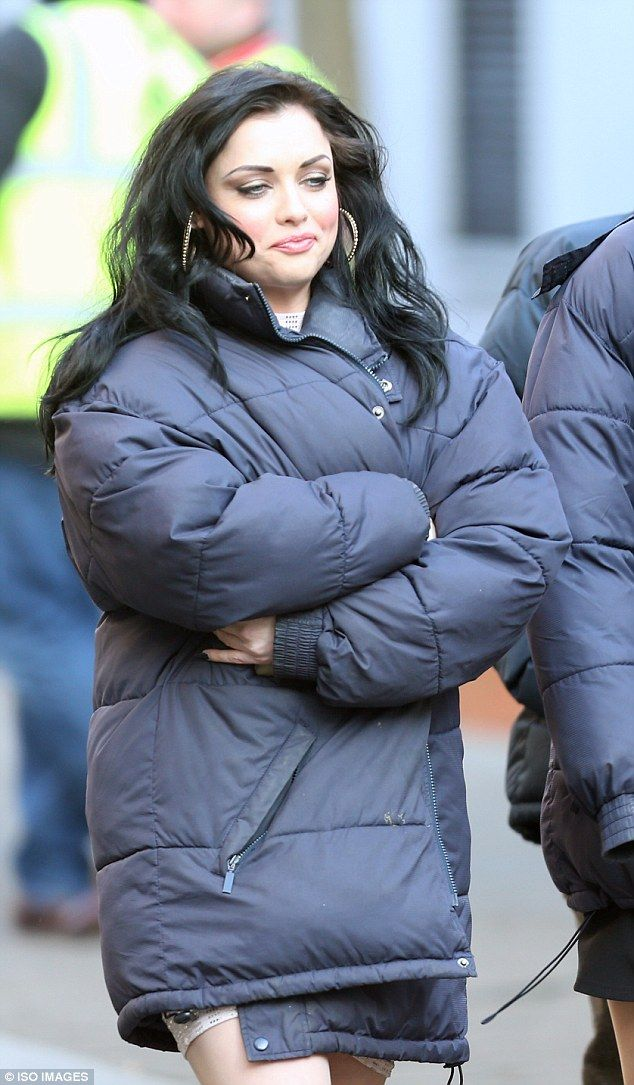Something to hide? Shona McGarty keeps her coat wrapped tightly around her as she shoots EastEnders scenes as Whitney Carter