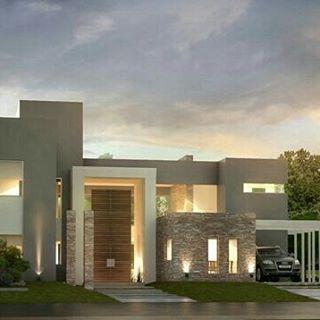Casa com volumetria variada, garagem lateral, porta de madeira e frente em pedra.