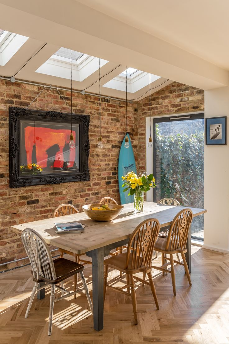 Side extension to residential home in Hove by three eleven design | home renovation | family room | dining | feature brick wall | surfboard | modern glazing | open plan | pendant lighting | velux roof lights | parquet floor | architectural photography | interior photography | architecture | interior design | howard baker photography
