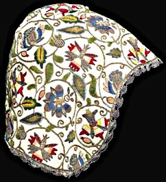 Embroidered coif  ENGLISH, CIRCA 1610  of fine linen embroidered with pomegranates, jonquils and violas with striped petals worked in coloured silk and gold and silver thread