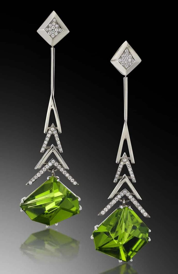 Crescendo Peridot Earrings feature two stunning peridot, cut by lapidary artist Tom Munsteiner, suspended from white gold forms, accented by diamonds. Call (949) 715-0953 or click for additional information.