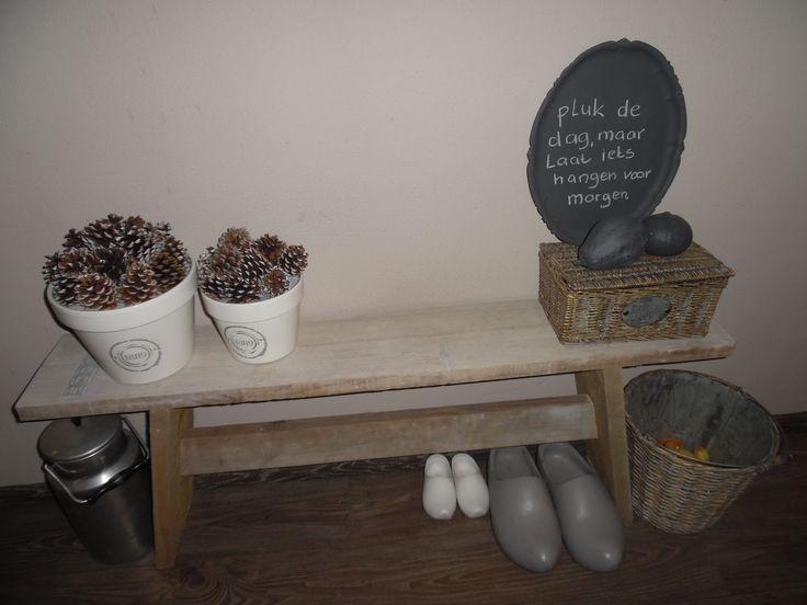 Een leuk bankje van steigerhout in de gang met daarop zelfgemaakte potten met dennenappels en een memotekstbord=een zilveren dienblad voorzien van schoolbordverf...