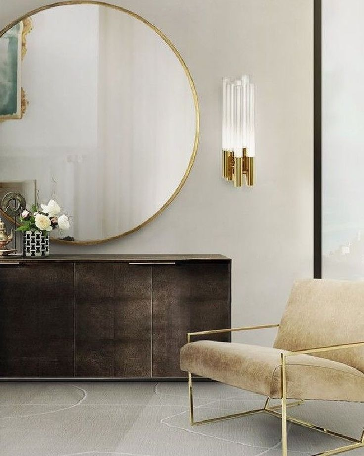 Simply perfect combination of masculine and feminine- old and new; round gold mirror, glass, old picture in the reflection, metal, and the sleek but masculine chest.