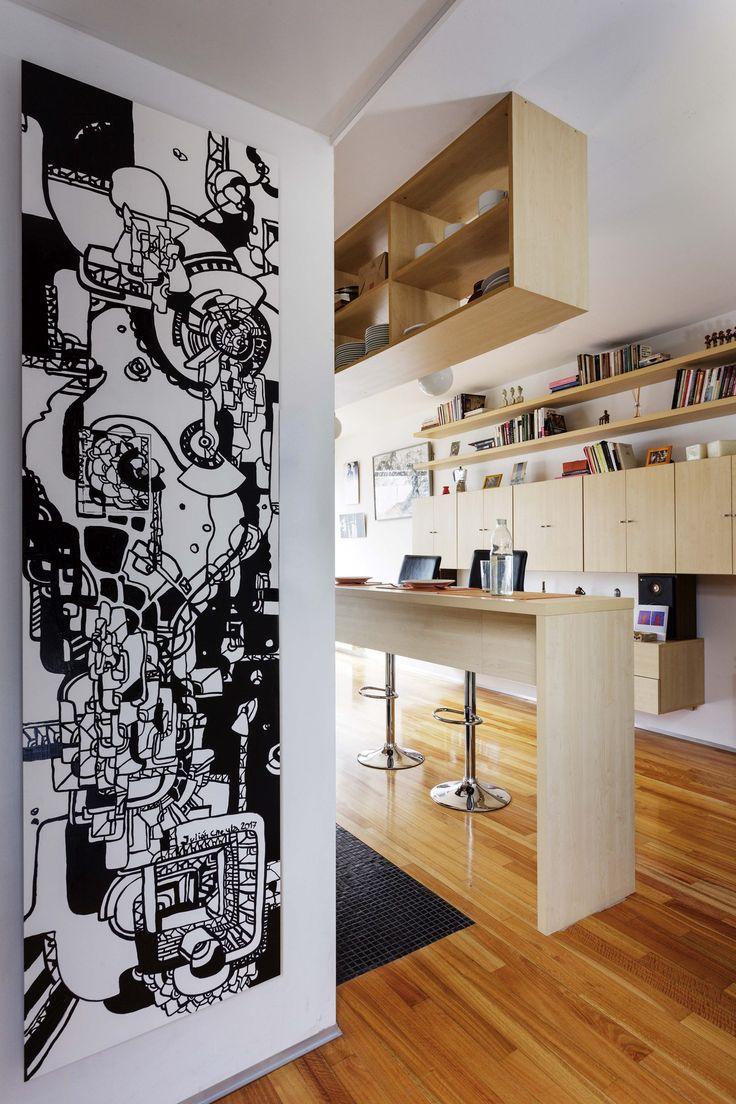 La entrada de este departamento da directo a la cocina comedor. En ella, una obra de Julián Cheula sobre la pared blanca.