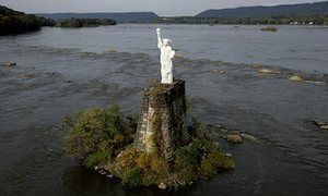 A mixed media replica of the Statue of Liberty rests on an old bridge piling in the middle of the Susquehanna River in Dauphin, Pennsylvania. This replaces a version that appeared in 1986 but was destroyed by bad weather in the 1990s