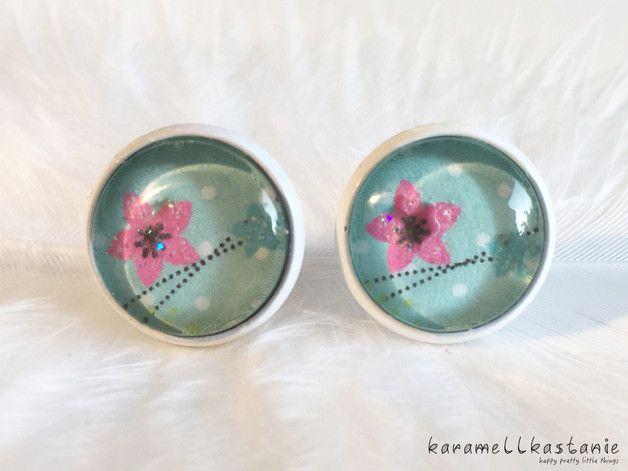Diese wunderschönen Ohrstecker haben einen frühlingshaft türkisfarbenen Hintergrund, auf welchem eine große pinkfarbene und eine kleine blaue Blume glitzern.  Durchmesser Cabochon inkl. Fassung:...