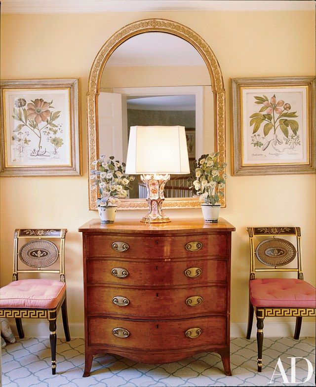 An English lamp with an urn base and tole cachepots top a chest of drawers in the master suite's vestibule