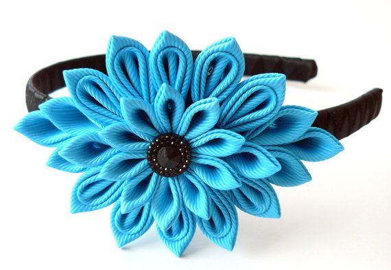 A flower is made in the technique of tsumami kanzashi. Plastic headband is weaved with black satin ribbon. Flowers are made from grosgrain ribbons.