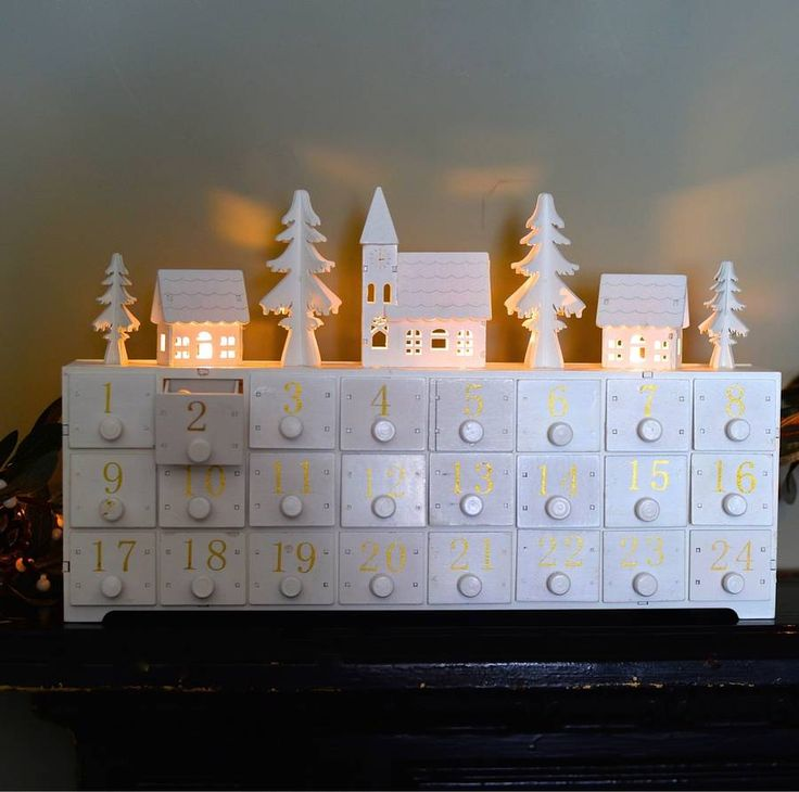 LED lit Wooden Advent Calendar with drawers.Make the age-old ritual of the advent calendar part of your loved ones' cherished Christmas memories with this charming wooden keepsake. The possibilities are endless for how you can fill the little drawers of this wonderful christmas box that lights up the village scene / animals on top with an LED light. White advent: The drawers have lovely gold numbers to add a little sparkle! Natural advent: This has lovely x mas pictures along side the…