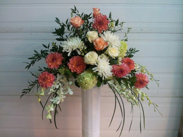 Coral and white dahlias mixed with roses and orchids.