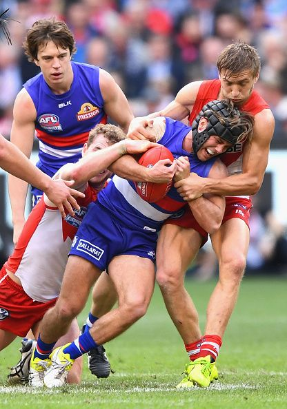 Caleb Daniel of the Bulldogs is tackled by Tom Mitchell and Kieren Jack of the Swans during the 2016 AFL Grand Final match between the Sydney Swans...