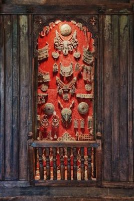 Doors open to reveal a display of tribal jewelry from Asia and the Middle East.