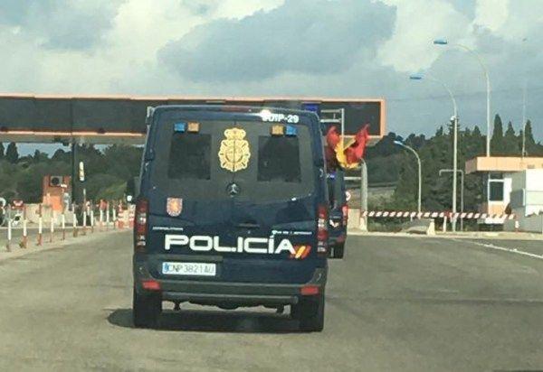 Un comboi de furgonetes de la Policia Nacional lluix la bandera espanyola al seu pas per Amposta