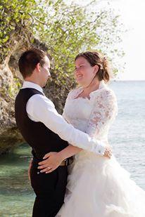 Romantische foto van dit bruidspaar op een zonnig eiland, je trouwkleding meenemen op huwelijksreis voor een fotoshoot is toch wel heel bijzonder.