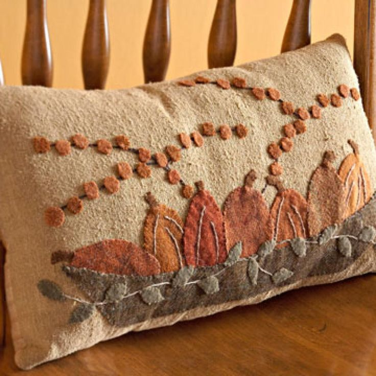 Combine embroidery with silk and wool fabrics to create a cozy pumpkin pillow for your fall decorating.