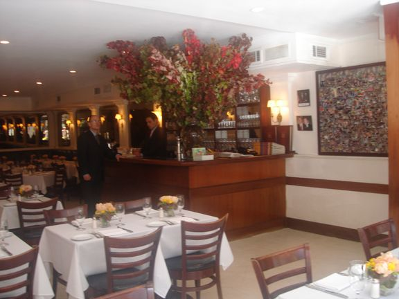 Nello, Madison Street, New York Low ceiling, framed mirrors around walls, beautiful and huge vase of flowers.