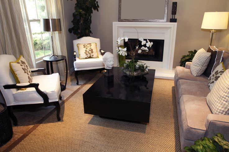 Professional design living room with white fireplace, rectangle dark block-style coffee table, two white armchairs with dark wood frames and one sofa facing windows.