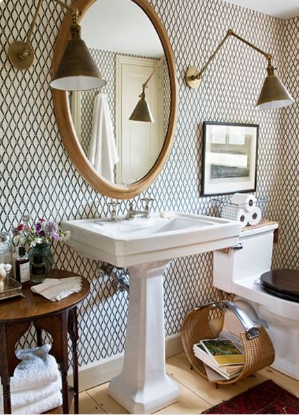{via Rita Konig} - LOVE the adustable wall scones here, the large oval wooden mirror, the geometric wallpaper, the dark toilet seat, antique wood table and fun wicker magazine rack