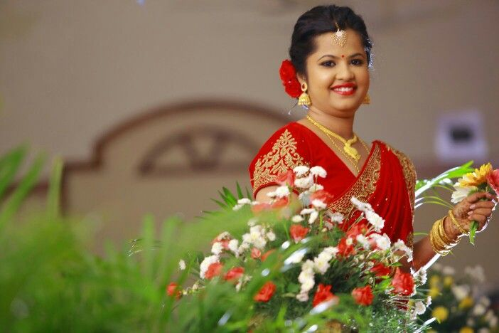 Bride for her reception, hair: messy with red roses, makeup: strobing