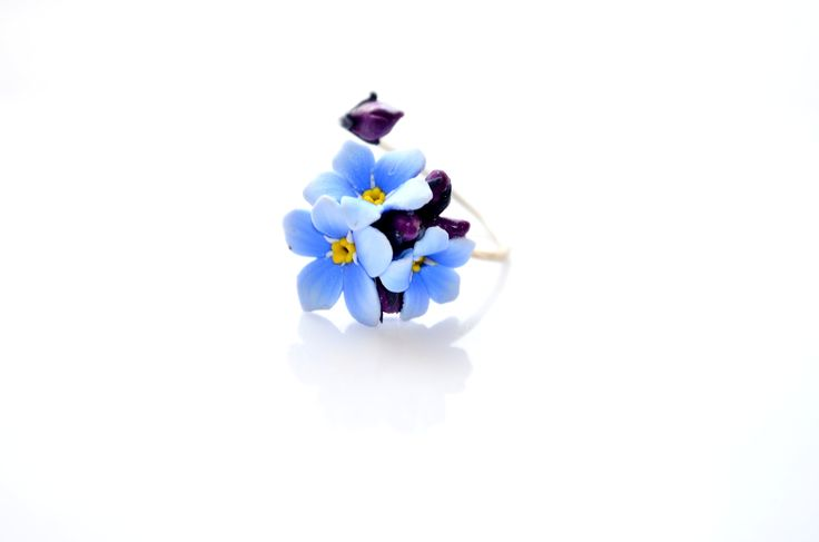 A beautiful ring with blue forget me not flowers handcrafted from polymer clay and sterling silver base By Innette innette.etsy.com
