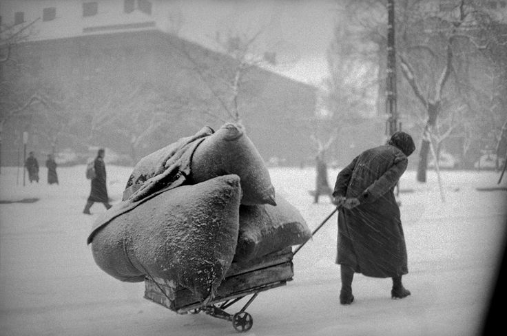 Erich Lessing - Budapest. 1956. A woman pulls three heavy sacks through the snow.
