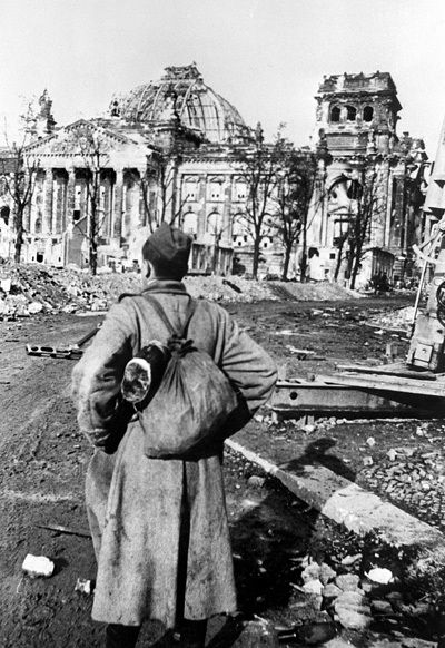 Soviet soldier private Mikhail Makarov looks at the destroyed Reichstag building in Berlin circa May 1945.