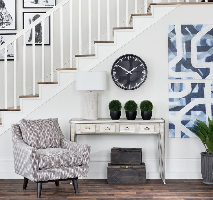 White entry way with medium wood floors, metal console table, geometric upholstered chair, blue and white canvas art, clock. Creative ways to display art