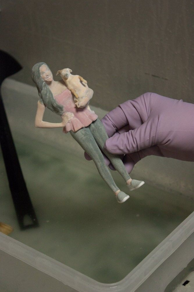 The printed 3D figurine takes a bath in a special lotion.