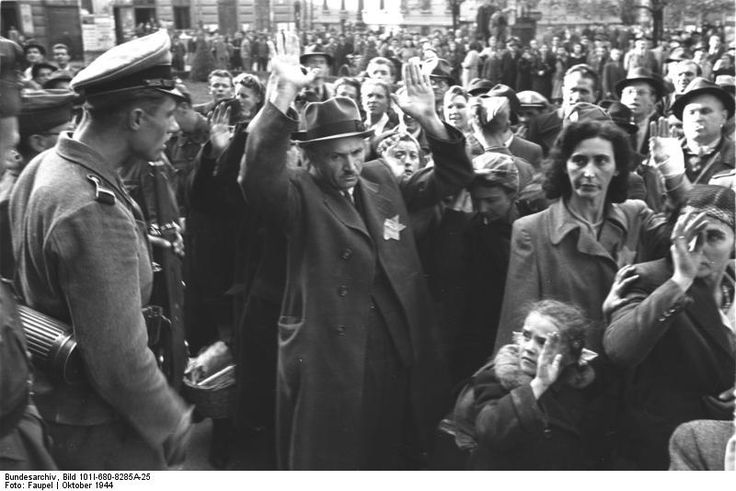 A tragically poignant photo of Budapest Jews being rounded up for deportation to death camps, Oct 1944.The SS bastard bellows orders to a terrified group of Jews to keep their hands up. Note the little girl in the right foreground. In the background there are Hungarians watching with apparent glee the fate of their Jewish co-citizens.An estimated 80,000 Budapest Jews were murdered by the Germans and their Hungarian collaborators in late 1944.