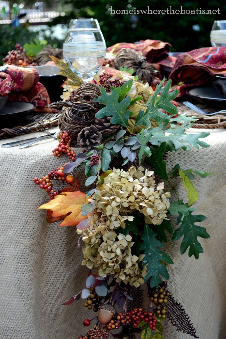 An artificial garland is serving as a runner on the table~  enhanced with addition of oak leaves, dried hydrangea blooms, grapevine pumpki...