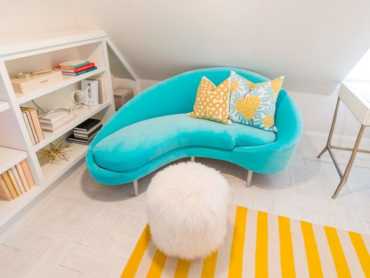 A plush velvet chaise lunge creates an inviting nook for the homeowner to relax and indulge in a good book. Yellow and white throw pillows and a coordinating throw rug enhance the cheery feel of the space.