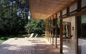 Smukt sommerhus med en terrasse og udhængslister af ubehandlet lærketræ. Det vil med tiden falme og blive gråligt.