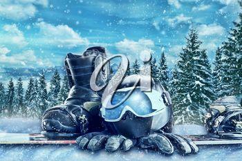 Winter sport glasses, ski, helmet and gloves on winter forest background