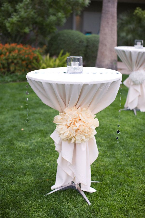 Love how they dressed up the table by adding the pom tie as well as the simple glass bead (?) runner. One candle and poof: simple elegance.