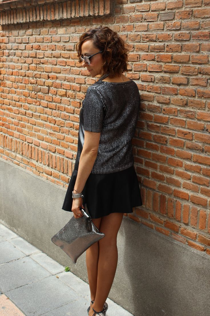 Falsa de piel en negro, bolso en plata, melena midi, ondas, jersey de punto negro y plata.
