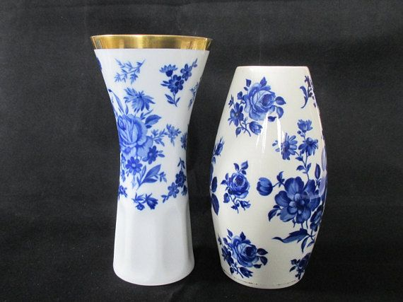 This set of two cobalt blue and white vase features coordinating images of flowers, and in contrasting shapes. Blue & white never disappoints, especially when its quality Bavarian porcelain. These beautiful blue & white flower vases will bring a sweet decorative element to your home. The taller of the two vases has almost an hourglass shape, with a beautiful gilt rim of gold. It stands just under 7 high, and the diameter at the rim is 3.25. The smaller vase is real cobalt, and has a g...