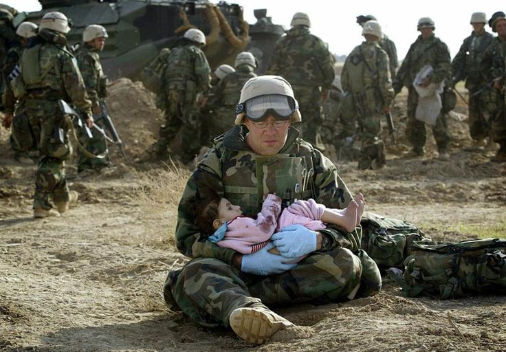 A US #Navy Hospital Corpsman holds a little girl after she was separated from her family during a firefight.