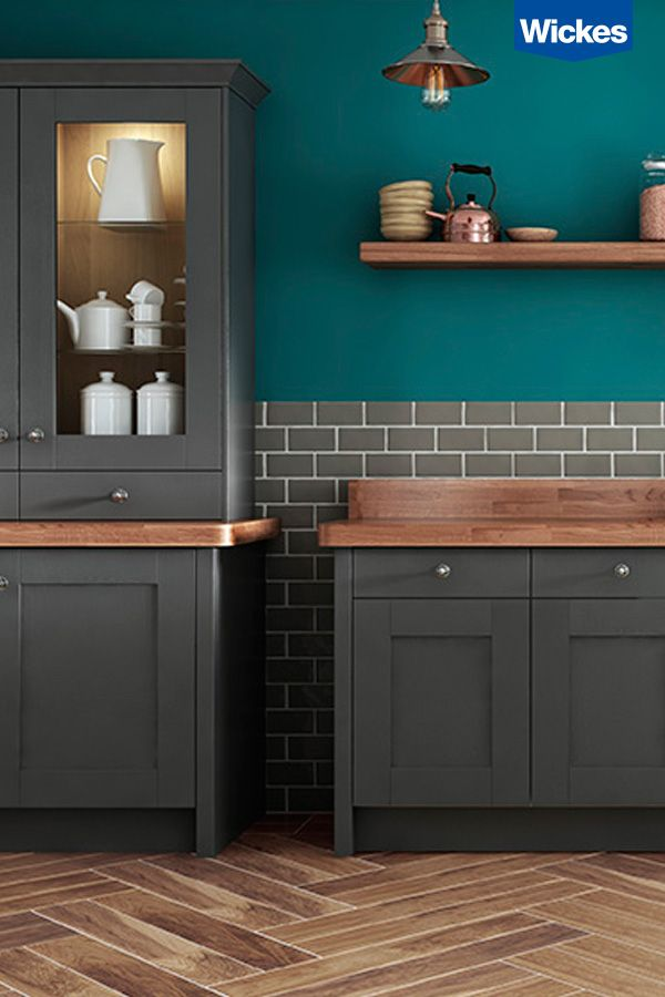 For an eclectic modern feel try mixing bold colours with natural tones and textures. This combination of deep oak worksurfaces and wood effect floor tiles effortlessly compliments the dark slate of the cabinets and the deep teal feature wall, forming a harmonious kitchen space. Open shelves and copper accessories add warmth and brightness to the look. Find your ideal kitchen at Wickes.
