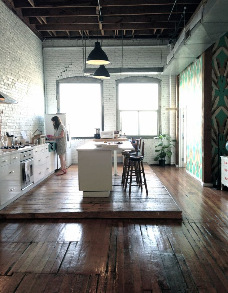 Rustic, original wooden floor boards are offset against the white metro tile walls and industrial white kitchen