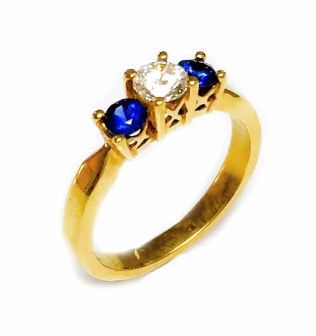 This isa three stones withcrossed prongsring, set with a diamond in the center and gemstones Blue Sapphires. The ring is set with a single diamond, round brilliant cut, 5.00 mm, white color in ranges of F-G, clarity is eye clean in ranges of VS-SI, total carat weight is 0.50 carat. The gemstones set in the ring are 2 natural Blue Sapphire, round cut, 3.50 mm, color is Royal Blue, clarity is eye clean or better, total weight carat is 0.25 carat.(This ring is available with any kind of…