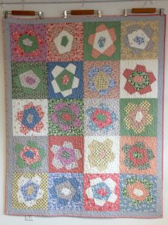 """50"""" x 62"""" this is sewn from 1930's style fabrics in happy colors.   It is machine pieced and machine quilted in an all-over meander texture.  The back of the quilt is a yellow check with tiny flowers.  the binding is hand stitched."""