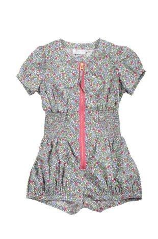 Braga corta para niña, en tela estampada con florecitas fucsia, lila y verdes. Cuello redondo, mangas cortas y cierre al frente.